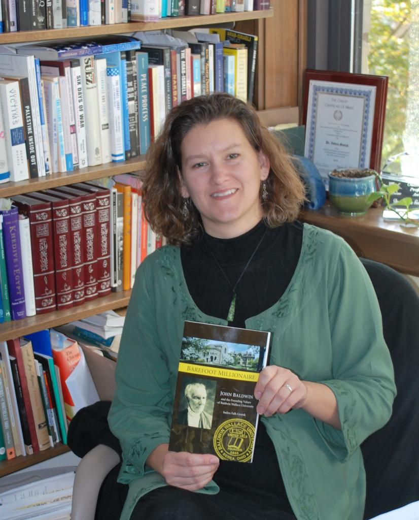 Dr. Indira Gesink of BW's History Department with her new book about BW's founder, John Baldwin.