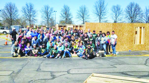 Student volunteers pose in front of the constructed frames at the Building Walls Event