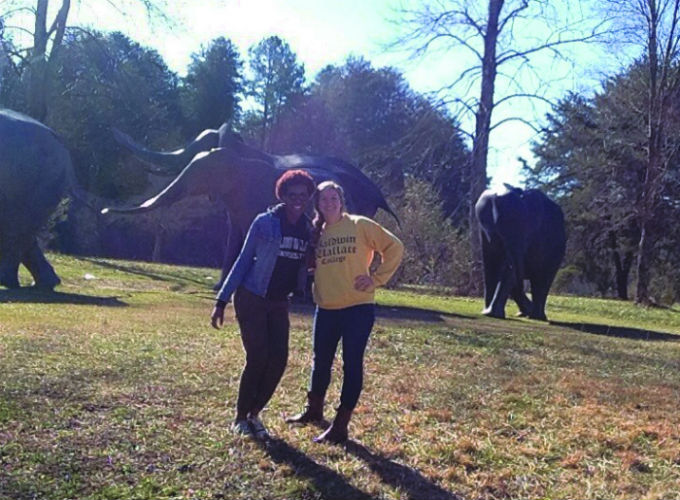 Keisha Butler and Caroline Dugan, '15, hang with elephants while on a field trip to the Asheboro Zoo.