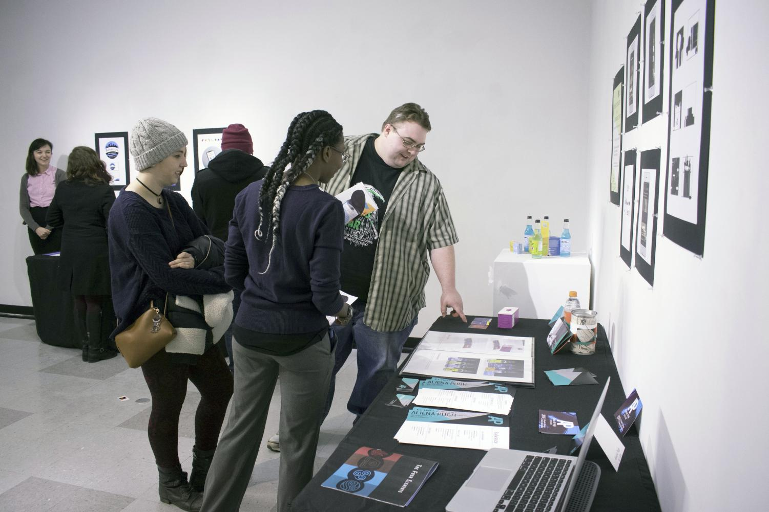 The graphic design seniors show and discuss their work in Fawick gallery during the opening reception on Friday, January 25 2019.